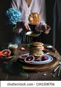 Morning breakfast with pancakes, blood oranges, strawberries on the black rustic background. Woman throws pancake up, flips pancake
