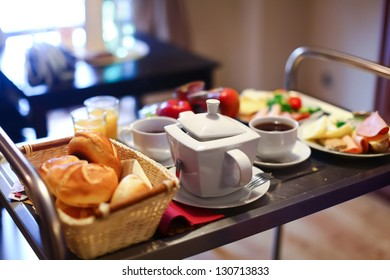 Morning breakfast. Served table with cups of hot tea, teapot, fresh bread, bun, croissant, plate with various cheese, ham, rolls, meat. Fruit mixed, orange juice, green salad, tomato.