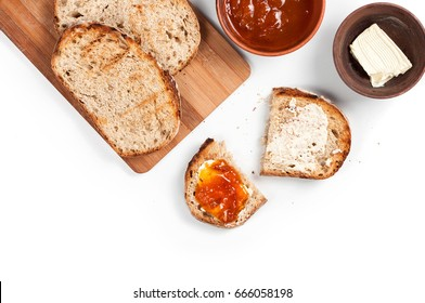 Morning breakfast table with fresh wholemeal homemade rural bread on a wooden cutting desk, apricot jam and butter. Isolated on white background. Top view, copy space.