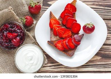 Morning breakfast. Toasts with strawberry and jam. Bread and confiture. Fresh hot toasts with cream. Delicious homemade dessert.
