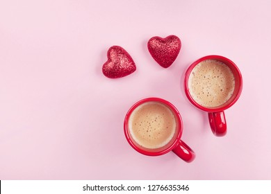 Morning breakfast for Valentines day. Two cups of coffee and red hearts on pink background top view. Flat lay.