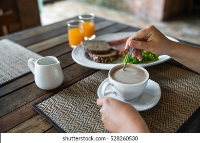 Morning breakfast. Woman mixing sugar in cappuccino with a spoon. Girl eating breakfast drinking orange juice in the morning. American breakfast in the cafe.