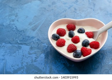 Morning Breakfast Yogurt with Berries Top View. Serving of Organic Sweet Dairy with Raspberries and Blackberries in Form of Heart Ceramic Bowl and Spoon. Healthcare Vegetarian Nourishment