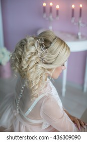 Morning of the bride. Beautiful blonde with hair and makeup, wedding dress, pink room, candles, flowers, decoration