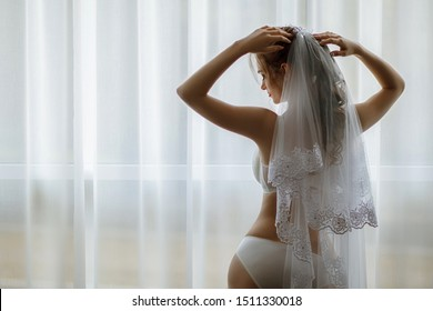 Morning bride. A beautiful girl with a white veil on her head stands near the window. Wedding portrait for the bride. Boudoir shooting. The bride in white beautiful underwear.