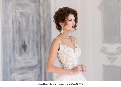 Morning of the bride. A beautiful bride stands in a wedding dress. Profile. Dress with lace. Large earrings with stones.