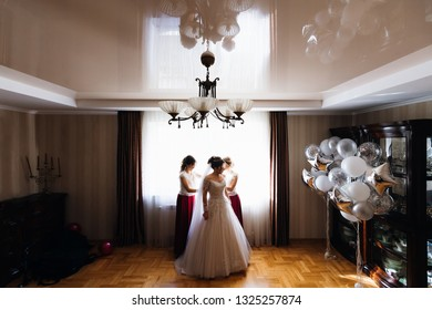Morning of the bride. bridesmaids dressing up a wedding dress in a room with a beautiful interior