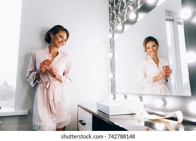 morning of the bride. The bride in front of the mirror in her dressing gown.