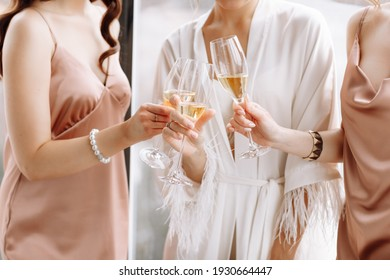Morning of bride. Gorgeous bride with best bridesmaids are holding glasses and drinking champagne in hotelroom near the large window. Sexy bridesmaids in exciting negligee. Wedding morning details.
