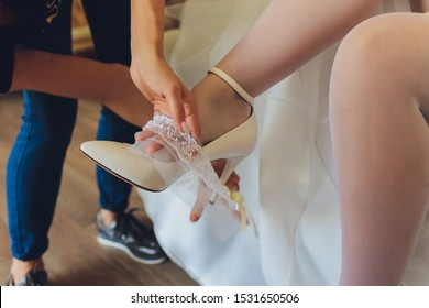 In the morning, the bride in stockings and a white wedding dress wears a garter on her leg, the bride is holding her hands for the garter.
