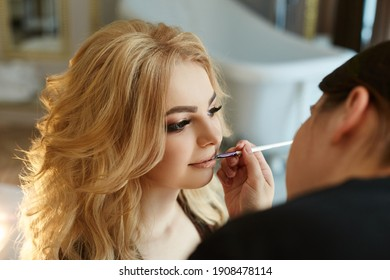 Morning of the bride. A woman in lingerie doing makeup to get ready for the wedding