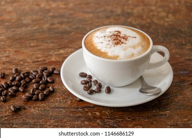 Morning cappuccino coffee​ and coffee bean on vintage wooden table