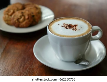 Morning cappuccino coffee and oatmeal cookies on wooden table