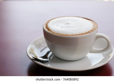 Morning cappuccino coffee on wooden? table and sunlight background