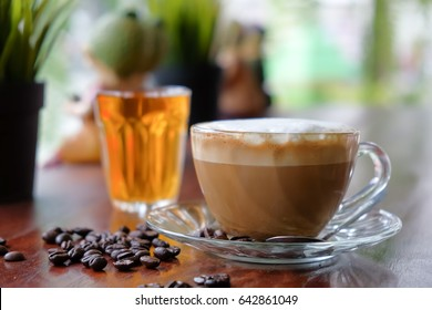 Morning cappuccino coffee and roasted coffee bean on wooden table and hot tea cup background