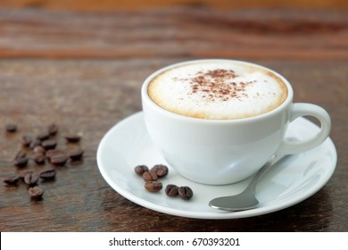 Morning cappuccino coffee and roasted coffee bean on vintage wooden table