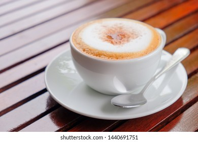 Morning cappuccino coffee​ on wooden​ table​ and light natur​ background