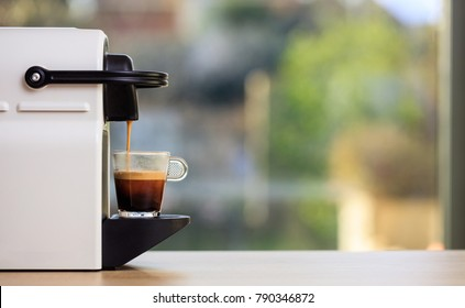 Morning capsule coffee. Espresso maker machine on a wooden table. Blurred background, space for text, front view