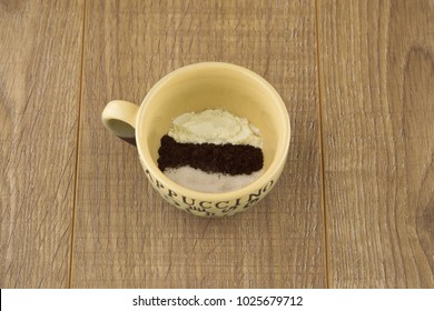 the morning charge of cheerfulness: ground coffee, dry non-fat creamer and sugar produced in mug for brewing this tasty drink, 3 in 1, side view