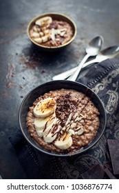 morning chocolate oat porridge with fresh bananas on black background