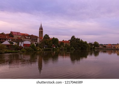 Morning cityscape of medieval Telc. Tower of Church of the Holy Spirit in Telc reflected in the water of the castle lake. A UNESCO World Heritage Site.