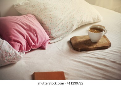 Morning coffee in bed. White coffee cup on wooden board, bed background. Soft pillows - star pattern & pink. Vintage color. Sleepy atmosphere. Place for text.