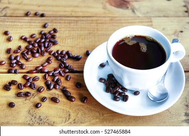 Morning Coffee, Black Coffee And Roasted Coffee Beans On wooden Table And Sunlight Background