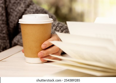 Morning coffee and a book. Woman holds a disposable coffee cup while reading a book