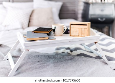 Morning coffee and breakfast on a tray with books in a cozy bed with a modern gray and white veil and pillows. An empty wooden calendar. Remote work at home, business and freelancing concept.