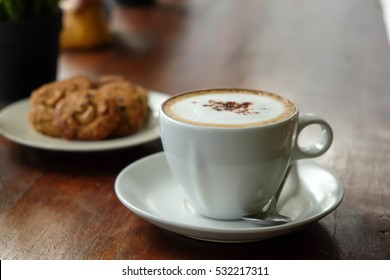 Morning coffee, Cappuccino coffee on wooden table and bakery background in coffee shop