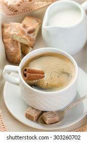 Morning coffee with cinnamon, milk, sugar and nut cookies (vertical shot)