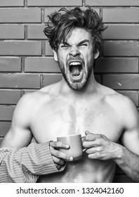 Morning coffee concept. Man with beard drink coffee brick wall background. Guy hold tea or coffee cup. Athlete sleepy face tousled hair wear bathrobe hold mug. Macho sexy torso enjoy coffee.