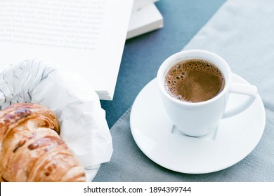 Morning coffee concept, white cup of coffee, empty book page, fresh baked croussant in paper pack on gray cloth and dark grey background