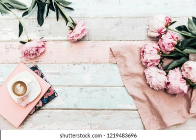 Morning coffee cup concept. Pink peony bouquet, coffee cup on vintage background. Top view, copy space
