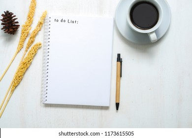 Morning coffee cup, notebook with to do list, pen and vintage rose flower on rustic table from above. Planning and design concept. Flat lay styling.