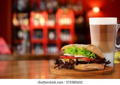 Morning coffee with fresh sandwich in restaurant