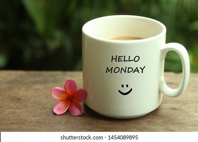 Morning Coffee. Hello Monday greetings concept with cute smiling face sign emoticon on a white mug of coffee and one little small beautiful pink Bali frangipani arrangement on wooden table.