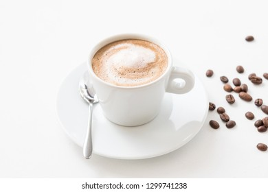 Morning coffee lifestyle. Hot invigorating drink. Latte cup with milk foam and beans on white background.