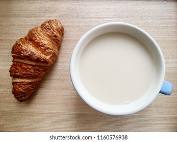 Morning coffee with milk and a croissant