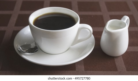 morning coffee with milk and sugar in a white cup on a table with a red cloth in a cagelife styleselective focus