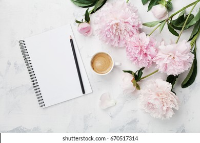 Morning coffee mug for breakfast, empty notebook, pencil and pink peony flowers on white stone table top view in flat lay style. Woman working desk. - Shutterstock ID 670517314