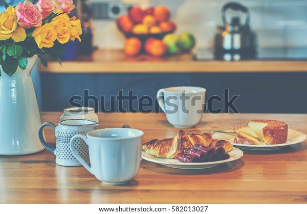 Morning coffee mug with croissant on rustic table, cozy and tasty breakfast, vintage toned.