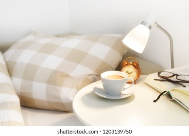 morning coffee on the bedside table, plus an alarm clock, lamp and book with glasses, lazy day concept, selected soft focus, narrow depth of field
