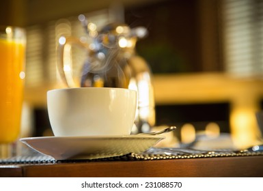 Morning at Coffee Shop in hotel with smoking hot mug. Decanter and orange juice very blurred. See more
