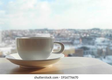 Morning coffee. White cup of coffee on table in cafe on blurred background with copy space. Selective focus, close-up.
