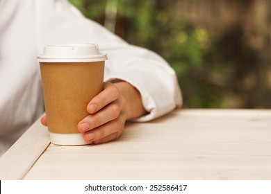 Morning coffee. Woman holds a disposable coffee cup