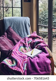 Morning coffee writing time at peacock cottage, with chair in a window alcove and pillows and blankets