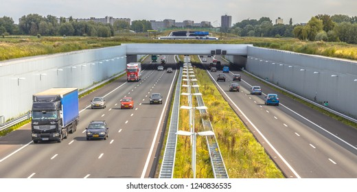 Morning commuting traffic on a4 motorway near The Hague Randstad area. Highway crossing aquaduct tunnel with urban area of Rotterdam in backdrop, Netherlands.