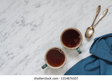 Morning composition with two cups of black coffee and blue napkin are on a marble surface with space for text, top view