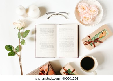Morning concept. Opened book, glasses, roses, vintage tray, gifts and coffee cup on white background. Flat Lay, top view, mockup